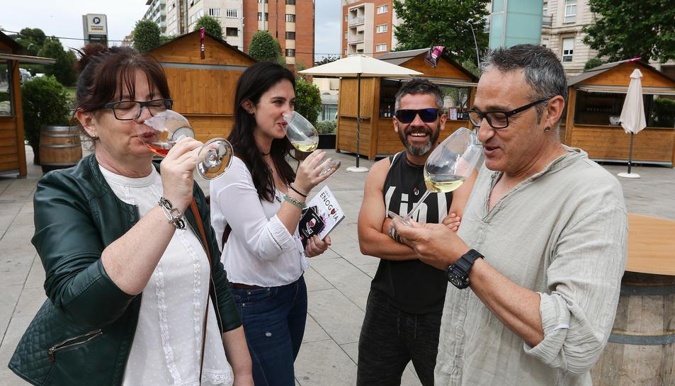 Assistents a la fira amb una copa de vi blanc.