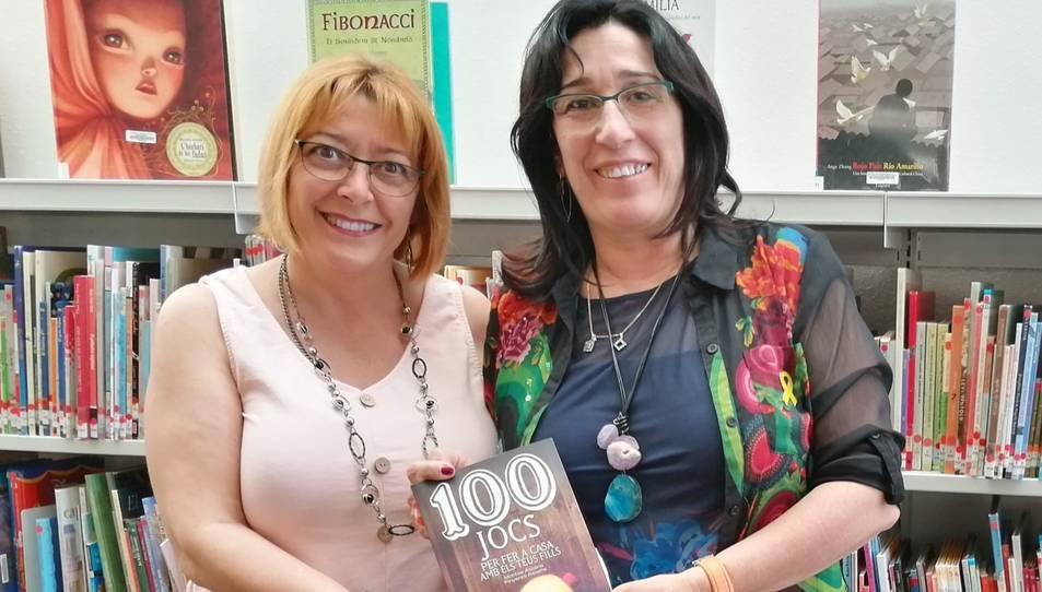 Pinyeres i Montse Assens amb el llibre que recull els jocs de la seva infantesa.