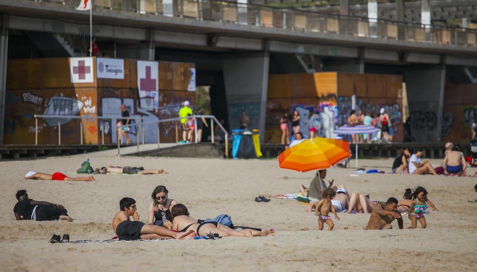Desenes de banyistes gaudien ahir d'un dia de platja a Tarragona.
