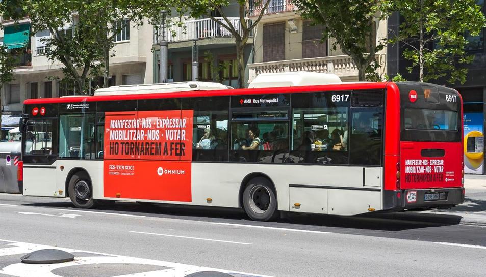 Pla general d'un autobús de TMB amb l'anunci d'Òmnium Cultural.