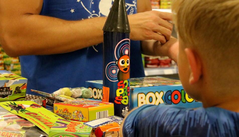 Pla escorç d'un nen observant el mostrador d'una botiga de petards els dies previs a la revetlla de Sant Joan.