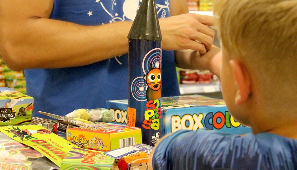 Un nen observant el mostrador d'una botiga de petards els dies previs a la revetlla de Sant Joan.
