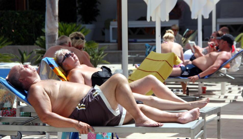 Una parella de turistes estrangers prenent el sol en unes gandules en un ressort de Cambrils.