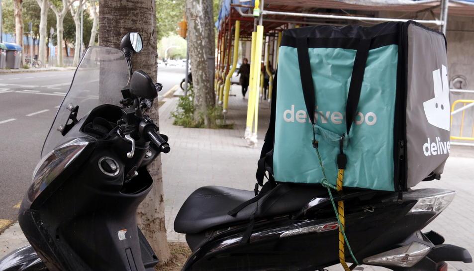 Una motocicleta de repartiment de menjar a domicili que fa el servei per a Deliveroo.