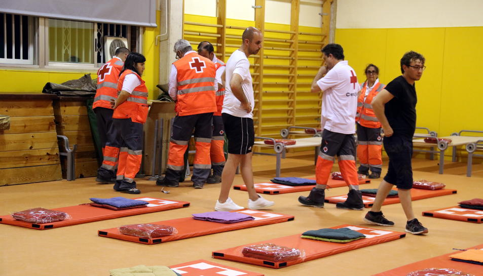 Pla general de l'aula esportiva de l'escola Enric Grau Fontseré de Flix amb els voluntaris de Creu Roja preparant tots els matalassos i mantes per dormir els desallotjats. Imatge del 27 de juny del 2019 (horitzontal)