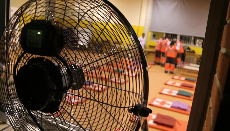 Primer pla d'un ventilador a la finestra de l'aula esportiva de l'escola Enric Grau Fontseré de Flix amb els voluntaris de Creu Roja preparant tots els matalassos i mantes per dormir els desallotjats. Imatge del 27 de juny del 2019 (horitzontal)