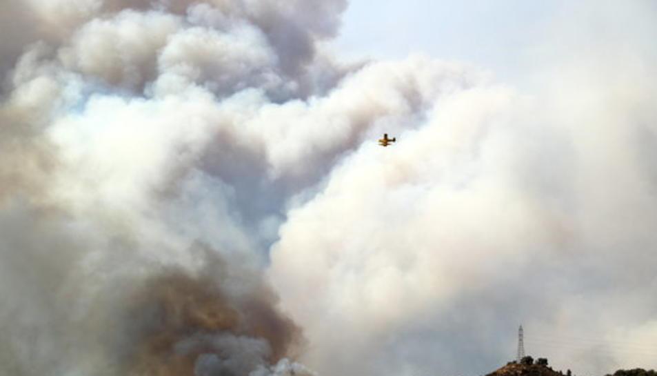 Un hidroavió sobrevola un gran núvol de fum d'un incendi forestal a la Ribera d'Ebre el 26 de juny del 2019.