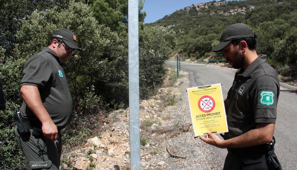 Dos efectius dels Agents Rurals a punt de col·locar un cartell que indica que està prohibit accedir a la serra del Montsec.