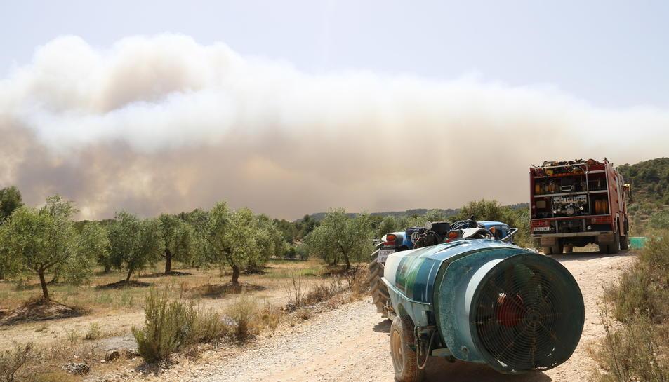 Pla sencer d'un camí de Bovera on es veu el fum de fons i hi ha un camió de bombers i una cisterna d'aigua.