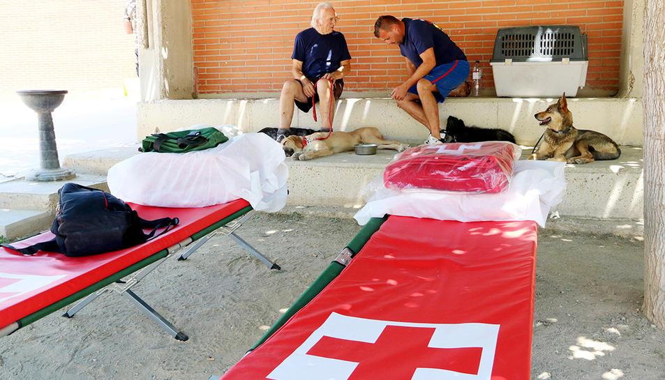 Diverses persones desallotjades, al pati de l'escola de Flix, amb diverses lliteres de la Creu Roja en primer terme.