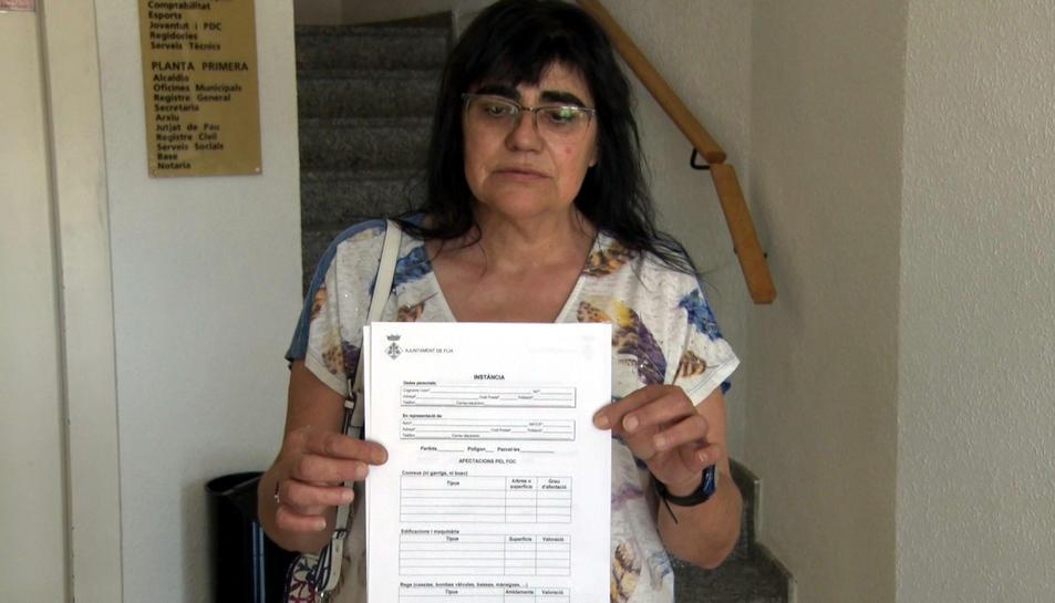 Maria Rosa Piñol amb el formulari de danys que reparteix l'Ajuntament de Flix per inventariar els desperfectes del foc.