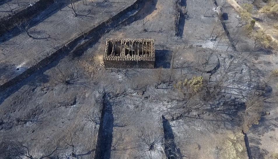 Pla aeri captat amb dron de la zona cremada per l'incendi de Ribera d'Ebre a Bovera on es pot veure un mas sense la teulada per l'efecte de les flames,.