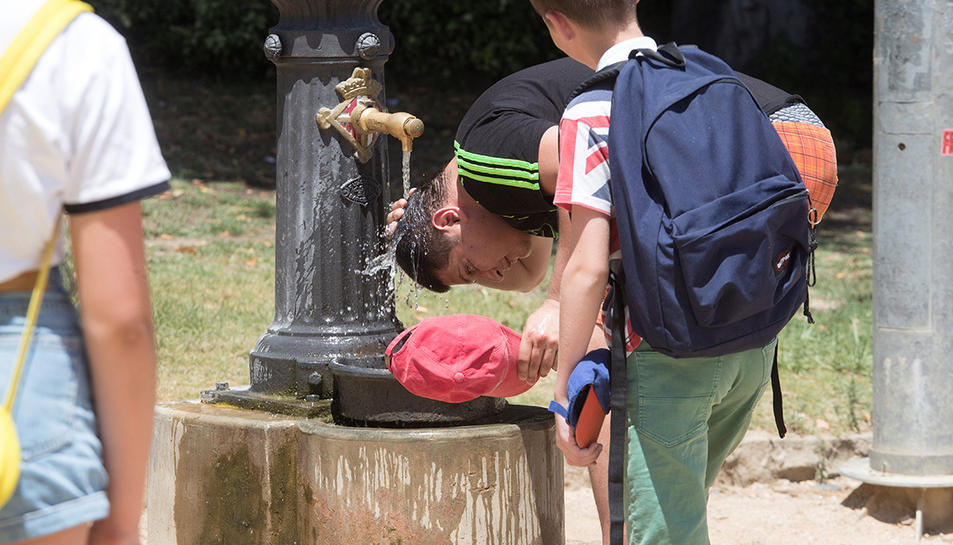 Un jove refrescant-se a una font a Barcelona.
