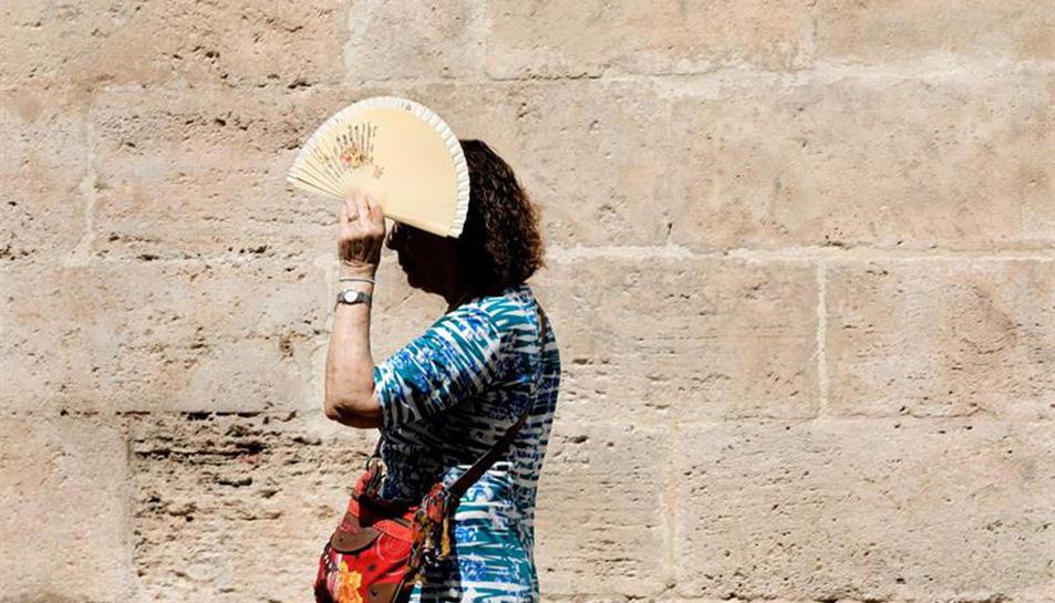 Imatge d'una dona protegint-se del sol amb un ventall.
