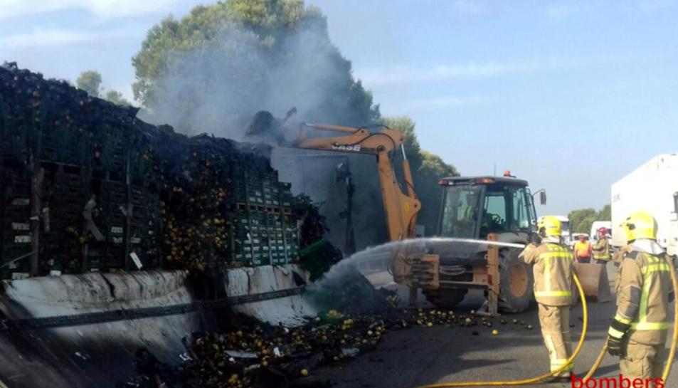 Diverses dotacions dels Bombers remullant la càrrega de llimones del camió.
