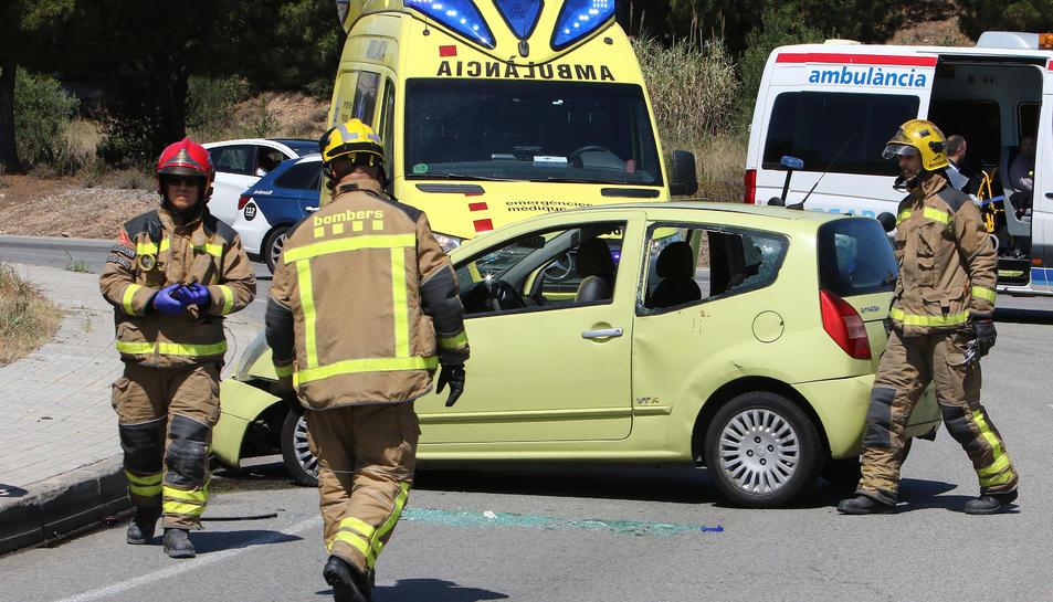 Imatge dels Bombers treballant en l'accident junt al cotxe que ha patit la col·lisió.