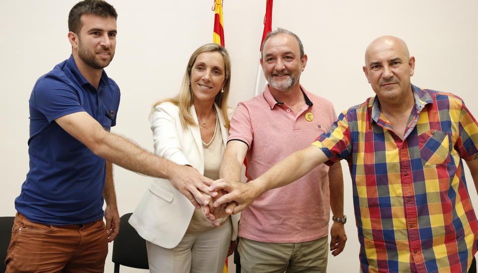 Encaixada de mans de l'acord a Valls, amb Ramon Giró, president local del PDeCAT, Dolors Farré, portaveu de JxValls, Jordi Cartanyà, d'ERC-Compromís per Valls, i Andreu Garcia, president local d'ERC.