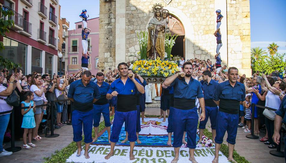Els portadors de la imatge, aturats damunt la catifa de flors i, al fons, dos pilars dels castellers.