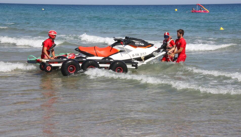 Els socorristes de la Creu Roja entrant la moto aquàtica a l'aigua, a la platja de l'Arrabassada de Tarragona.
