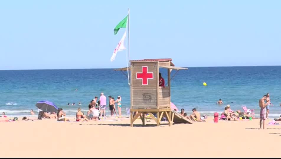 Una bandera verda onejant a una platja.
