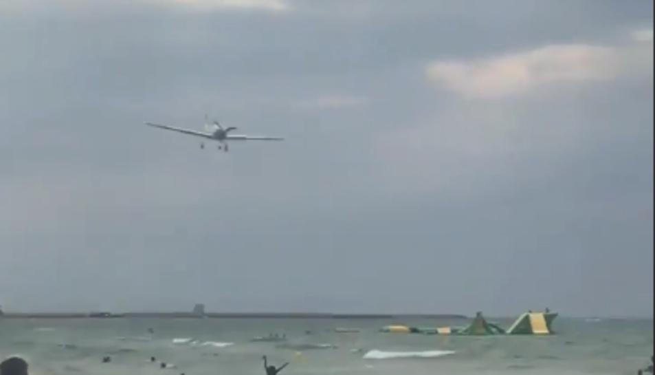 Imatge de l'avió sobrevolant els banyistes a la platja de Calafell.