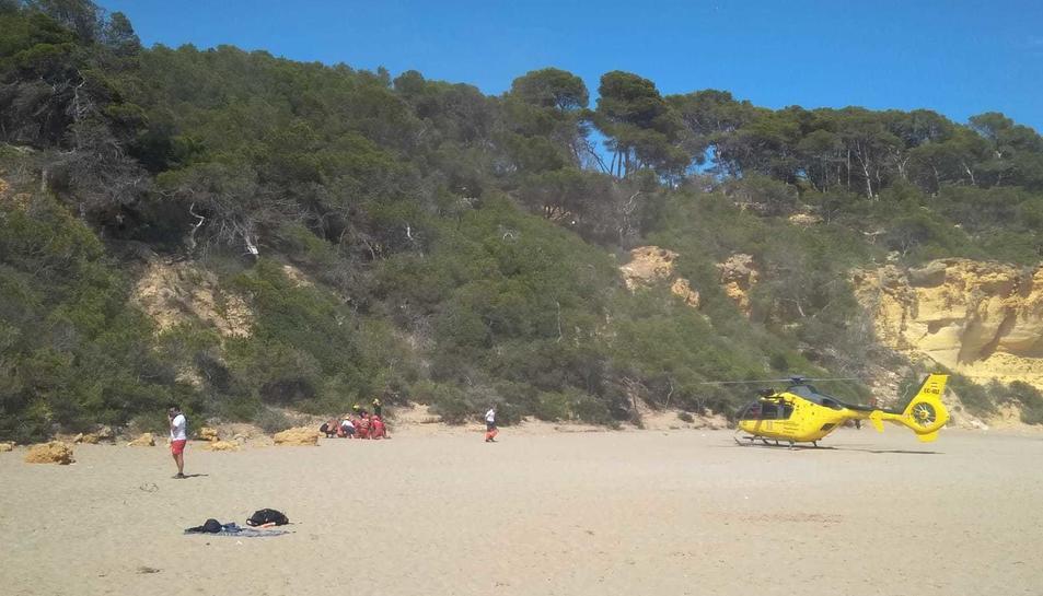 L'helicòpter dels bombers a la sorra poc abans de pujar l'accidentada.