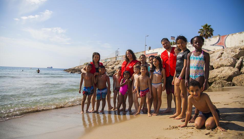 Fotografia família dels nens del casal d'estiu amb els monitors de Creu Roja, ahir, a la platja del Miracle.