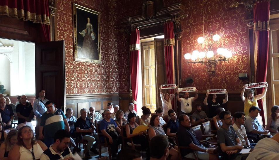 Imatge del públic del ple. Algunes persones mostren la pancarta 'Llibertat presos polítics'.
