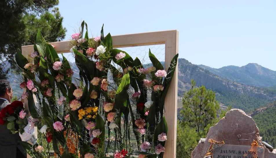 Pla general del monòlit en record als cinc bombers morts a Horta el 2009 amb el panell amb clavells que s'han dipositat aquest diumenge per tancar l'acte d'homenatge, deu anys després de la seva mort. Imatge del 21 de juliol del 2019 (vertical)