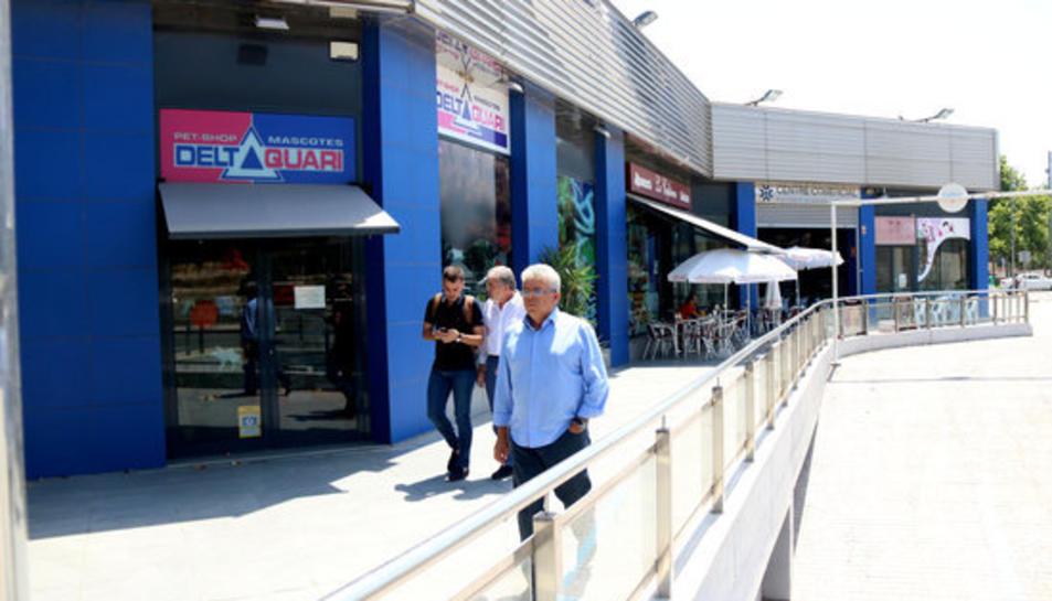 Els responsables de Family Cash davant de les galeries comercials després de la signatura del compromís de compra-venda.
