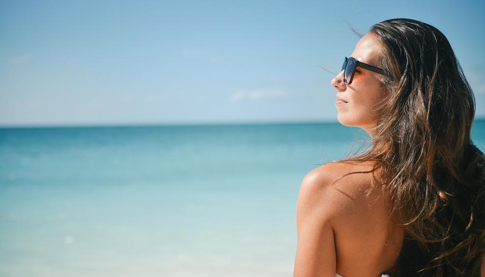 Imatge d'una noia protegida amb ulleres de sol i barret.
