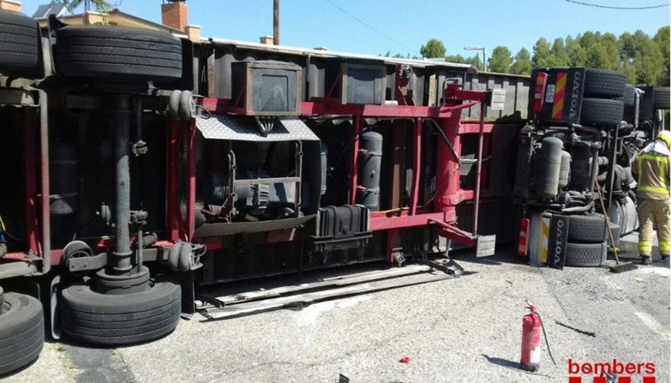 El camió ha quedat bolcat a la via.