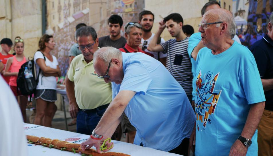 L'Eduard tallant l'entrepà amb unes tisores, com sempre ha fet a Can Boada.