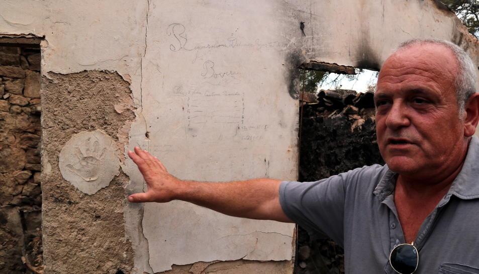 El pagès Enric Prunera assenyalant una de les parets del seu mas que es va salvar de les flames.