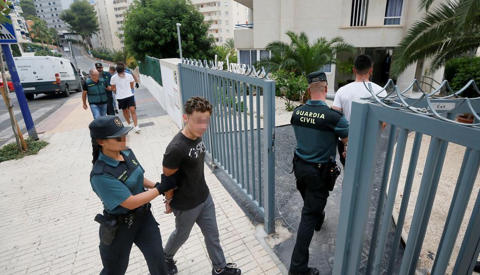 Els detinguts per una presumpta agressió sexual en grup a Benidorm entren custodiats a l'edifici on van succeir els fets.