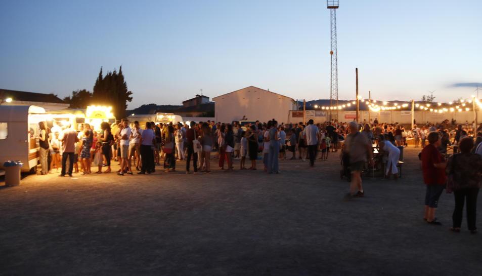Pla general de multitud de persones al Festival de Cinema de la Terra Alta, amb 'foodtrucks', barra de bar i música en directe a la zona esportiva de Bot.