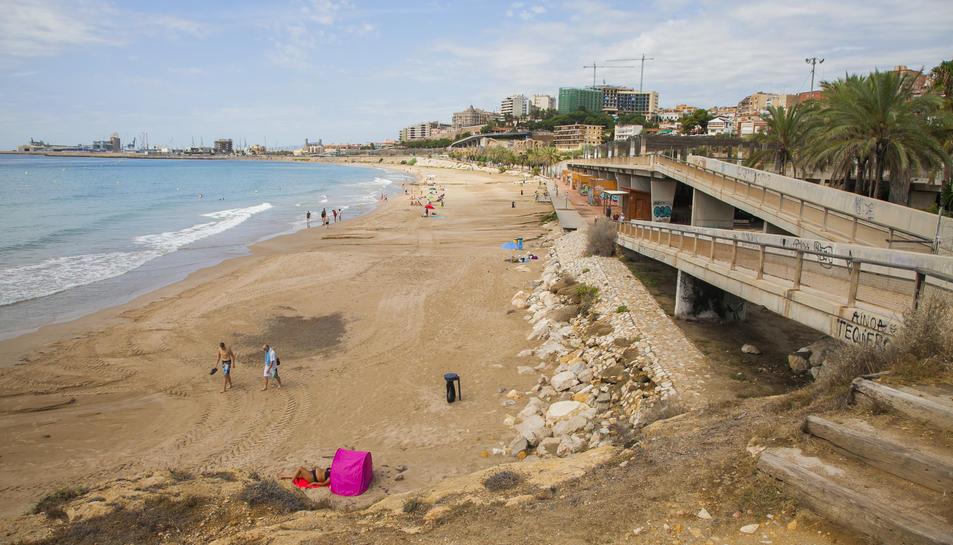 Pla general de la platja del Miracle, amb la plataforma tancada al públic a la dreta.