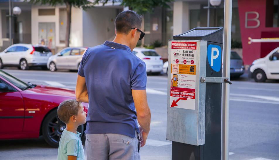 Un home i un nen, ahir, davant d'un dels parquímetres afectats al carrer Vidal i Barraquer.