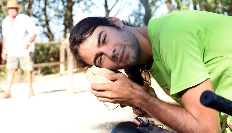 Pla mitjà de l'artista Òscar de la Fuente escoltant la sonoritat d'una pedra al camí de sirga d'Amposta.