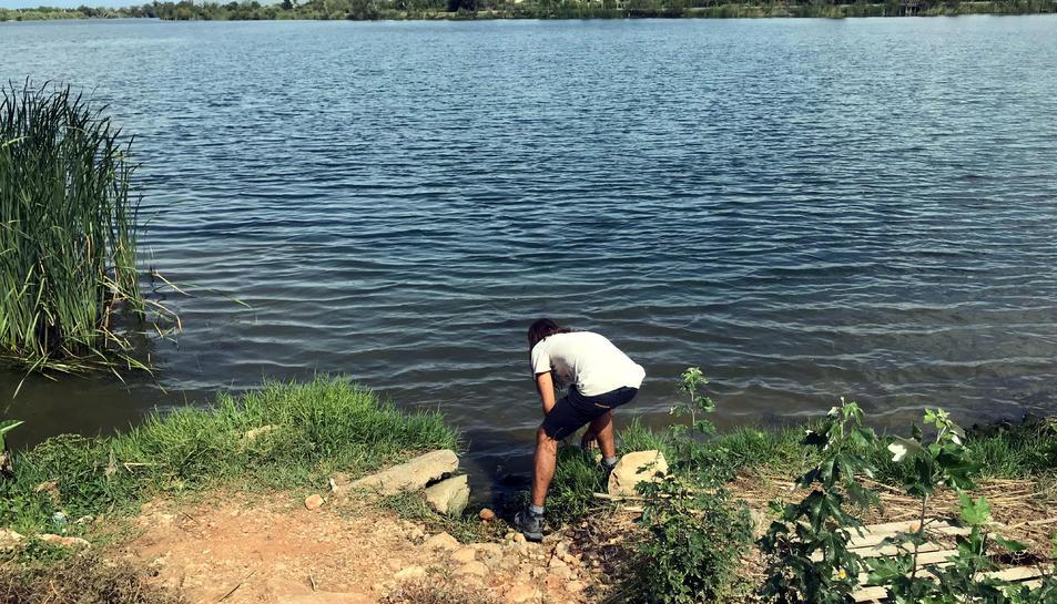 L'artista Òscar de la Fuente buscant una pedra al riu Ebre per convertir-la en altaveu de la sonoritat de l'entorn.