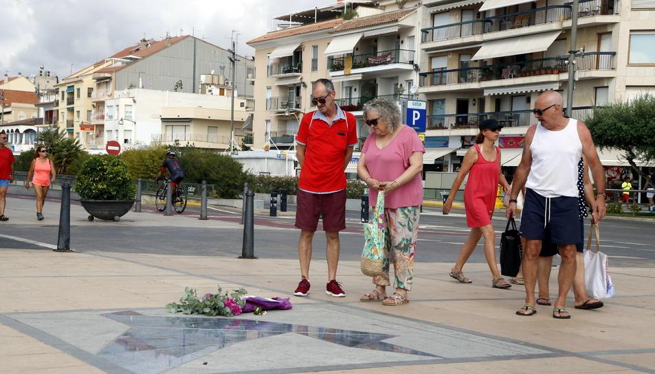 Pla obert de diverses persones aturades davant del Memorial per la Pau de Cambrils, amb un ram de flors.