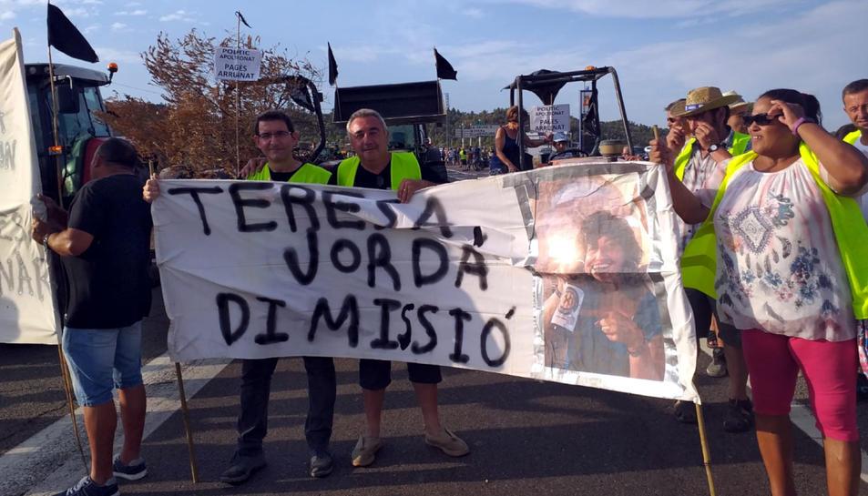 Pla general d'un grup de manifestants afectats pels focs del juny mostrant una pancarta que demana la dimissió de la consellera Teresa Jordà, el 18 d'agost del 2019 (horitzontal)