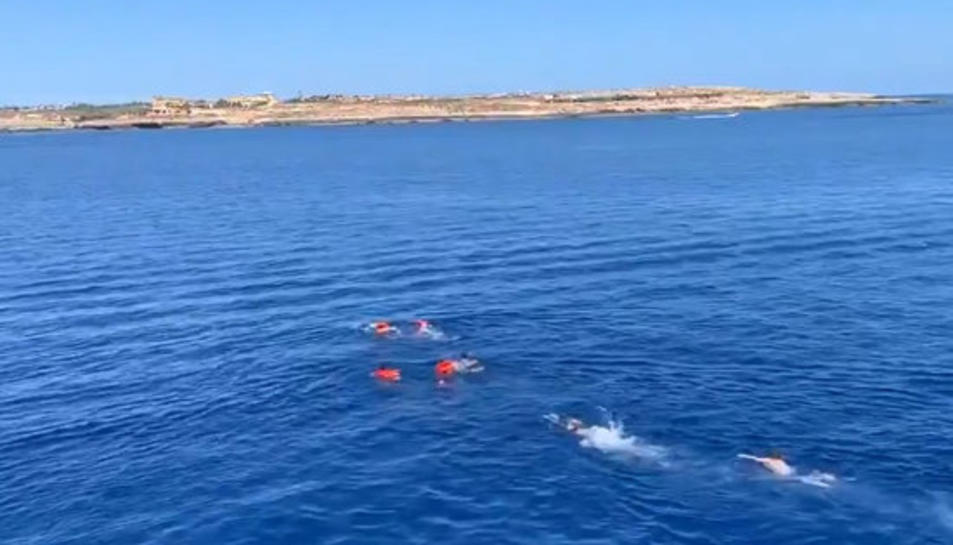 Quatre rescatats per l'Open Arms es llencen a l'aigua i són perseguits per socorristes, amb la costa de Lampedusa al fons.