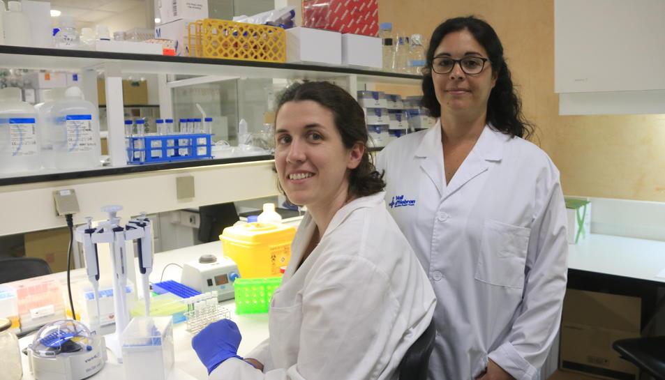 La doctora María José Buzón, del Grup de Malalties Infeccioses del Vall d'Hebron Institut de Recerca (VHIR) (dreta), amb una altra investigadora de l'equip, Laura Luque (asseguda), al laboratori.
