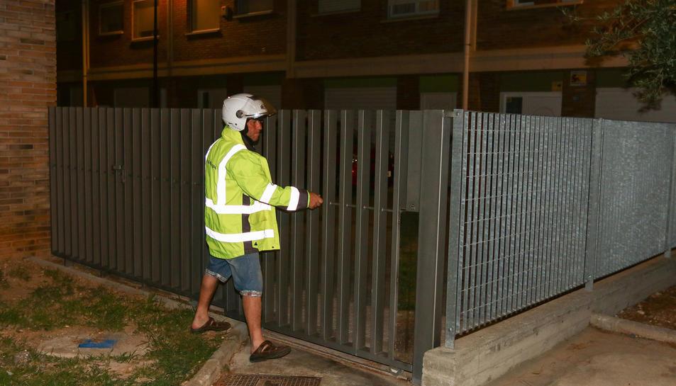 El treballador que, ahir a la nit, feia córrer la tanca per barrar l'entrada de persones.