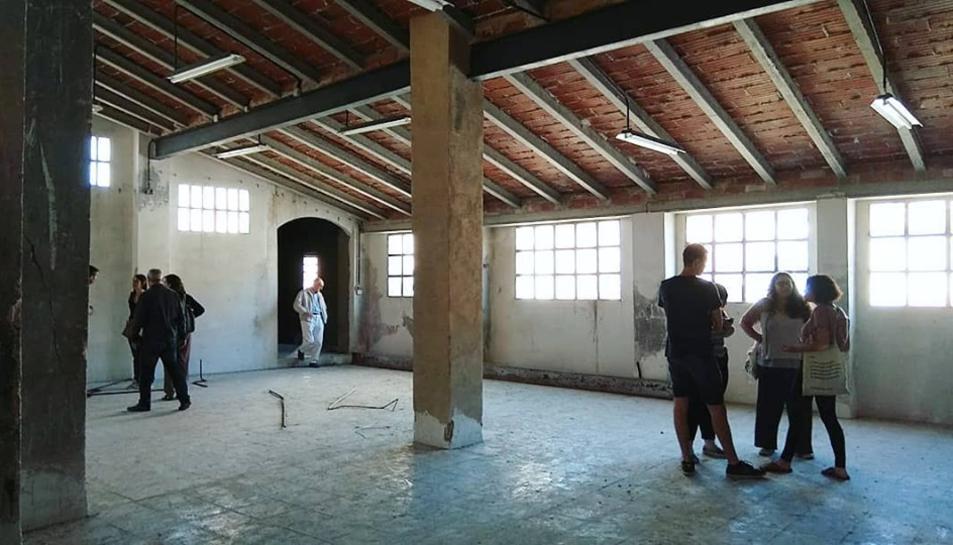 Persones recorrent l'interior d'un antic immoble del centre històric de Valls que s'integrarà en una promocíó d'habitatges socials gestionats per la cooperativa La Titaranya.