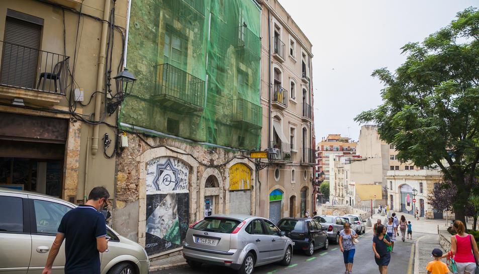 Estat que presenta la façana del número 21 de Baixada de la Peixateria, coberta amb una lona.