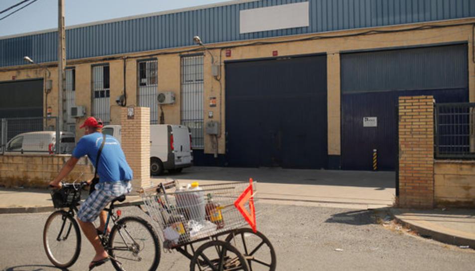 Un home passa amb una bicicleta a prop de la fàbrica Magrudis a Sevilla, focus del brot de listeriosi.
