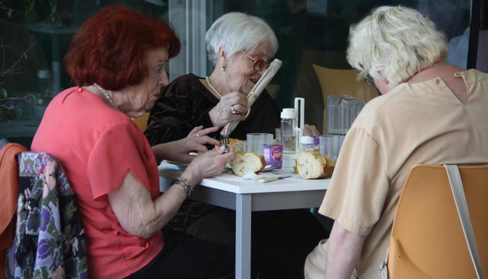 Imatge d'arxiu d'un grup de persones grans compartint taula.