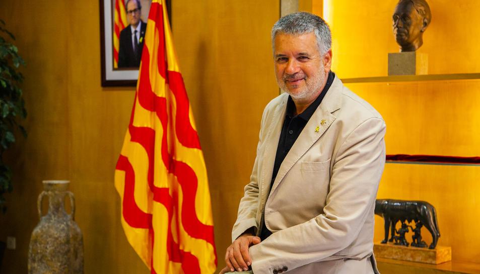 Pau Ricomà al seu despatx a l'Ajuntament, amb les imatges dels presidents de la Generalitat Quim Torra i Lluís Companys al darrere.